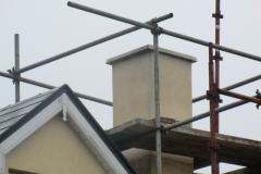 Existing chimney stack and scaffolding at roof level for safety